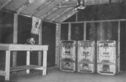 A view inside an Army kitchen shack. Three M1937 gasoline-fired field ranges are positioned on the back wall.