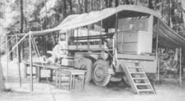 An Army kitchen truck set up to serve a meal in the forward area.