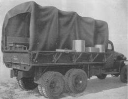 A side view of an Army kitchen truck. The troop seets have been relocated to outside the truck to give the cooks storage shelves.